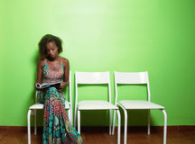 African american woman reading magazine in waiting room of docto. Beautiful african american woman reading magazine in waiting room of doctor Royalty Free Stock Photos