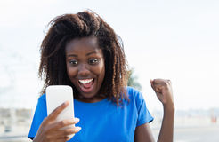 African american woman receiving good news by phone Stock Photo