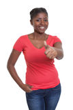 African american woman in a red shirt showing thumb up Stock Photo