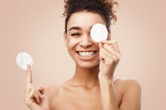 African-american woman removing makeup with cotton pads. On light background royalty free stock images