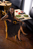 African American woman at a restaurant. Attractive African woman in a restaurant Royalty Free Stock Photo