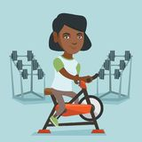 Young african woman riding stationary bicycle. Stock Images