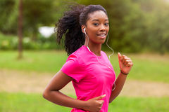 African american woman runner jogging outdoors - Fitness, peopl Stock Photography