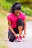 African american woman runner tightening shoe lace - Fitness, pe Stock Images