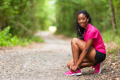 African american woman runner tightening shoe lace - Fitness, pe Royalty Free Stock Photography