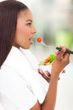 African american woman salad. Side view of pretty african american woman eating green salad at home Stock Photo