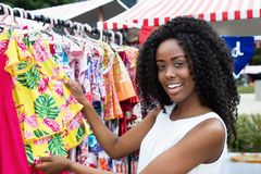 African american woman selling colorful clothes at market. African american woman selling colorful clothes outdoors at typical traditional market Royalty Free Stock Photography