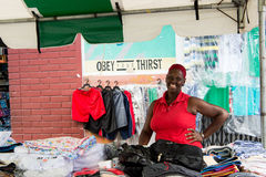 African American woman sells shorts. Port of spain, Trinidad and Tobago - November 28, 2015: smiling woman with red hair african American sells many cloths of Royalty Free Stock Photography