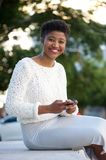 African american woman sending message with cellphone. Smiling young african american woman sending text message with cellphone outdoors Royalty Free Stock Photo
