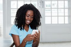 African american woman sending message with phone Royalty Free Stock Image