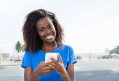African american woman sending message with phone. Outdoor in the city in the summer Royalty Free Stock Photos