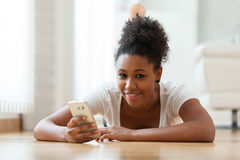 African American woman sending a text message on a mobile phone Royalty Free Stock Photo