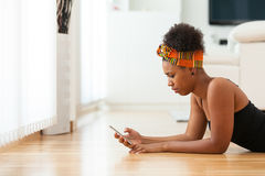 African American woman sending a text message on a mobile phone Royalty Free Stock Photography