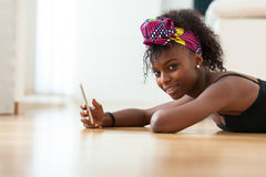 African American woman sending a text message on a mobile phone Stock Images