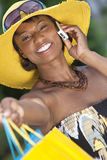 African American Woman, Shopping Bags & Cell Phone. Beautiful and Fashionable African American woman with colorful shopping bags, smiling and talking on her cell Stock Image