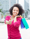 African american woman with shopping bags showing thumb Stock Image