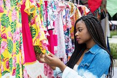 African american woman shopping colorful clothes at market. African american woman shopping colorful clothes outdoors at typical traditional market Royalty Free Stock Photos