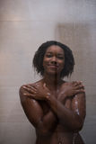 African American woman in the shower. Woman in the shower,beautiful black young female showering under refreshing water, healthy lifestyle, enjoying time in Royalty Free Stock Image