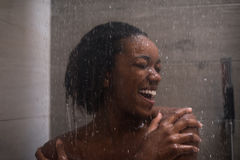 African American woman in the shower. Woman in the shower,beautiful black young female showering under refreshing water, healthy lifestyle, enjoying time in Royalty Free Stock Photography