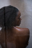 African American woman in the shower. Woman in the shower,beautiful black young female showering under refreshing water, healthy lifestyle, enjoying time in Stock Photos