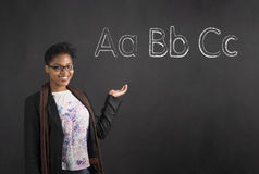 African American woman showing the ABC alphabet against blackboard Stock Photography