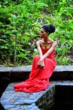 African-American woman sitting on a background of green plants. African American girl in a red dress, with dreadlocks sitting on a background of green plants on royalty free stock image
