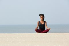 African american woman sitting at beach in yoga pose Stock Photography