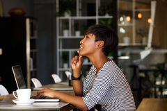 African american woman sitting at cafe with laptop Royalty Free Stock Photos