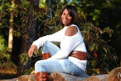 African-American woman sitting on log. Smiling stock photos