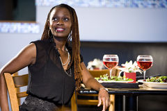 African American woman sitting at restaurant table stock photo