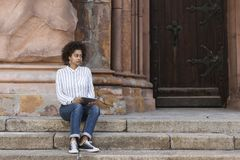 African-American woman sitting on the steps near the building. She looks straight and holds the tablet stock images