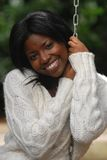 African-American woman smiles. While sitting in a swing stock photography