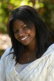African-American woman smiles. While enjoying a fall day royalty free stock images