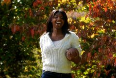 African-American woman smiles with a football. African-American woman enjoys sports outdoors and a game of football. While enjoying the fall season stock images