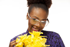 African American woman smiles while holding fresh flowers. An African American woman with glasses holds her fresh picked flowers close to her face royalty free stock photo