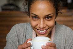 African american woman smiling with cup of a coffee Royalty Free Stock Photos