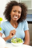 African American woman smiling. African American woman smiling eating a salad Royalty Free Stock Photos