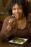 African American woman smiling eating a salad. African American woman living a healty lifestyle Royalty Free Stock Images
