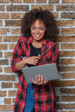 African american woman smiling and holding laptop. Young african american woman smiling and holding laptop royalty free stock images