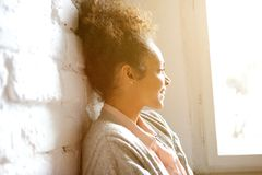 African american woman smiling and looking out of window Royalty Free Stock Photos