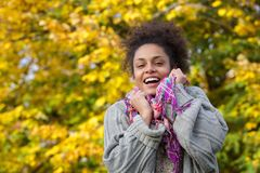 African american woman smiling with sweater and scarf in autumn Stock Images
