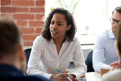 African American woman speaking at company meeting. African American women speaking, offering ideas at company meeting, briefing, female employee expressing royalty free stock photography