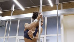 African American woman is spinning sexually around a dancing pole. Dancer with seductive gaze rotates at vertical bar in a spacious hall in a sporty tight stock video