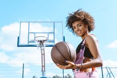 African-american woman in sports bra and pink overalls holding a basketball ball. At sports court stock images