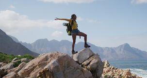 African american woman standing on rock with arms wide open while trekking in the mountains