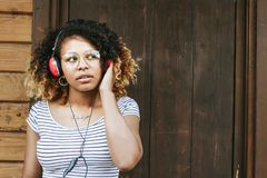 Woman outdoors  with headphones. African American woman in striped top standing outside the door of her home wearing headphones with red  earpieces listening to Stock Photo