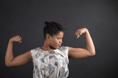 African American woman with strong arms on blackboard background Stock Photo