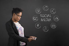 African American woman with tablet social networking on blackboard background Stock Photo