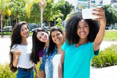 African american woman taking selfie with phone and internationa. African american women taking selfie with phone and international girlfriends outdoor in the Stock Photos