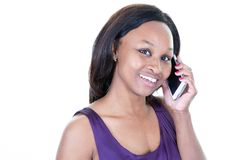 African American woman is talking on her phone on white background. An African American woman is talking on her phone on white background royalty free stock images